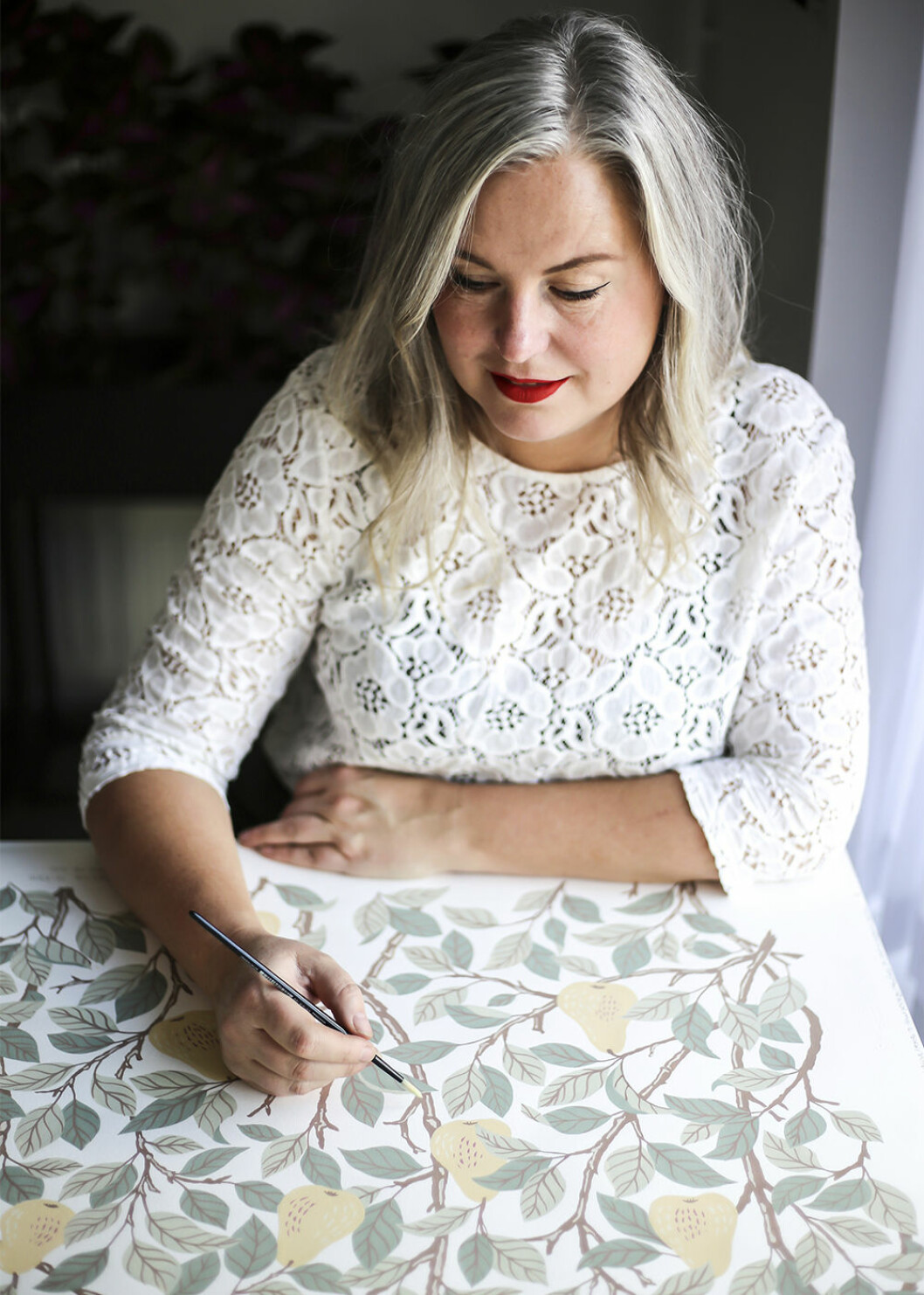 Hanna Wendelbo vid ritbordet med en av hennes tapeter