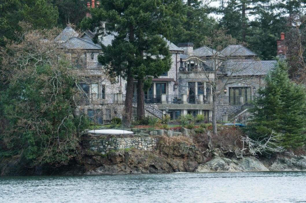 Ett stort grått hus i sten som ligger dolt bland träd och med vatten framför