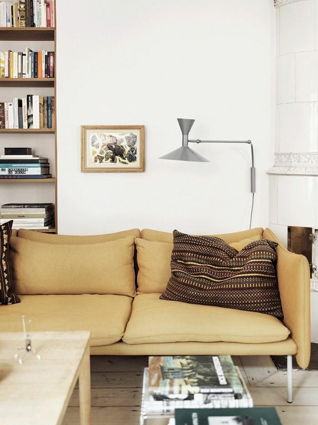 """Det krävdes lite övertalning av kvinnan i affären för att välja den gula färgen på soffan, """"men nu älskar vi den!"""". Lampan är designad av Le Corbusier för Nemo Lightning."""