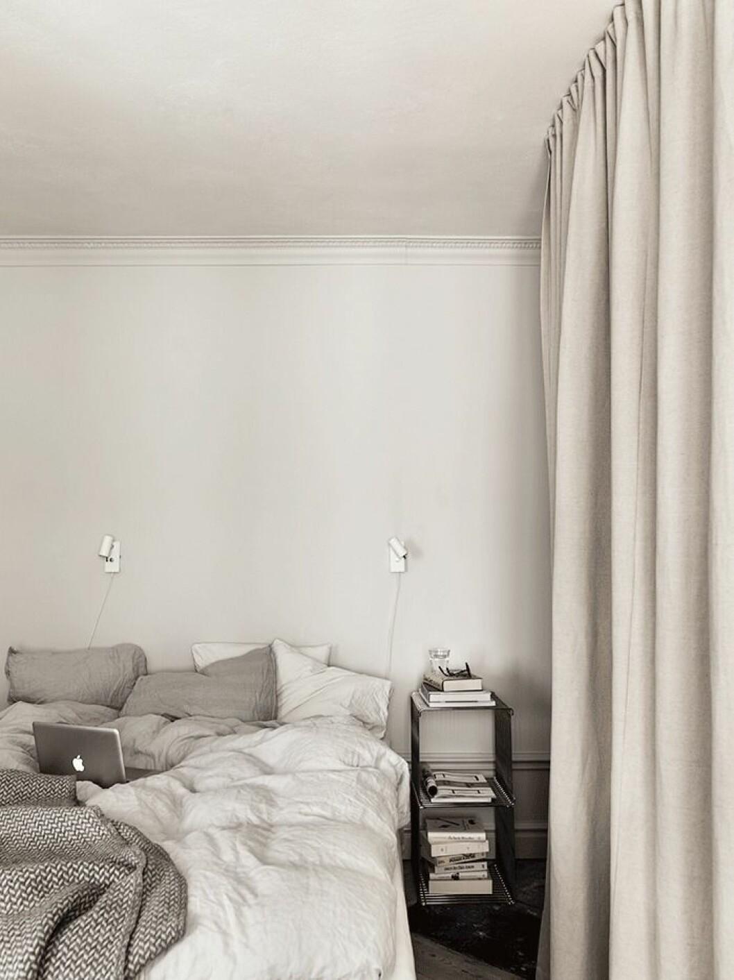 Sovrummet är avskalat och rofyllt inrett. Längs ena väggen finns väggfast förvaring bakom ett draperi från Tygverket. Sängborden är moduler av Verner Panton, Montana, och lampan Cato tillverkas av Belid.