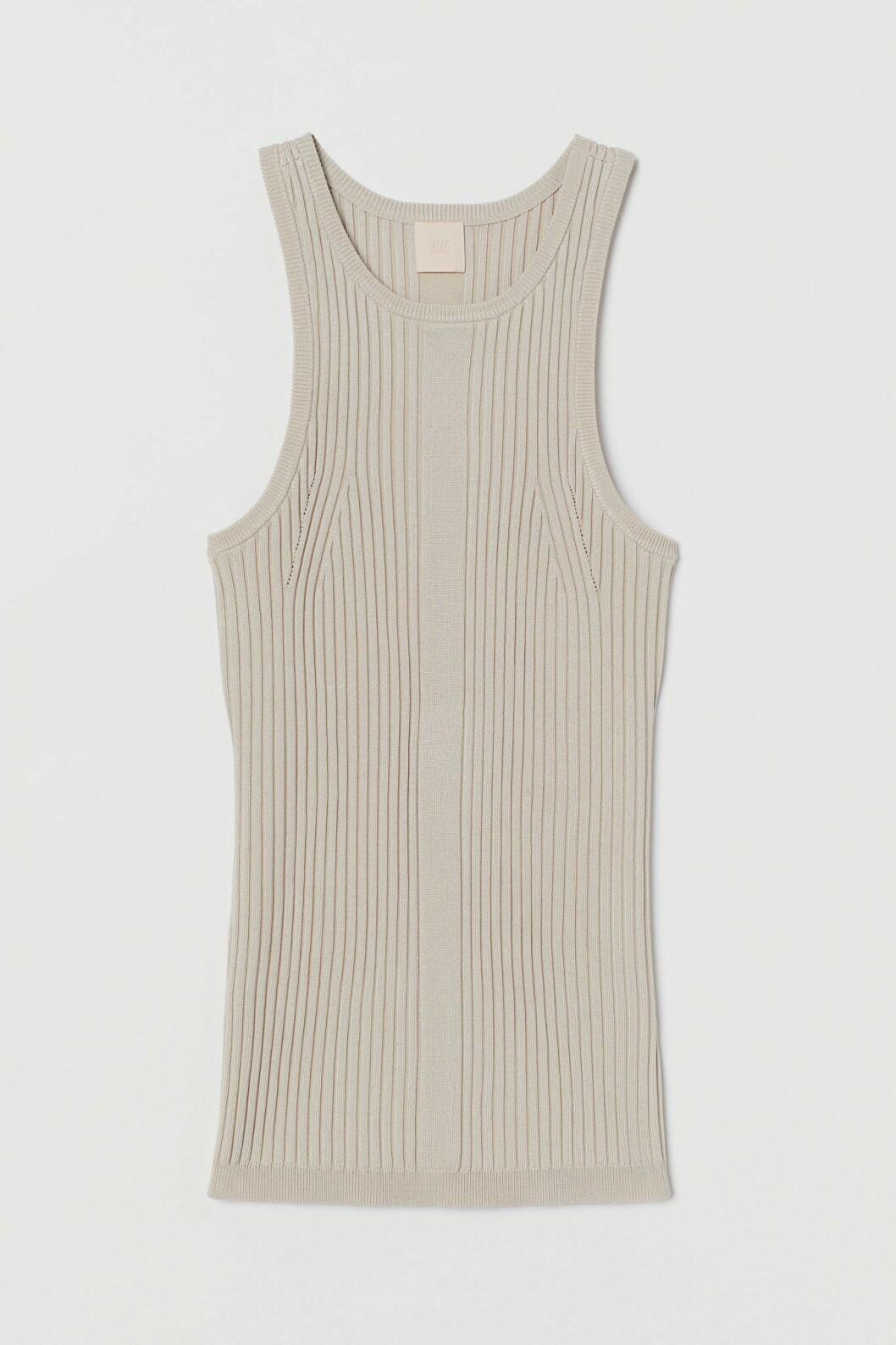 Bär ett ribb-stickat linne med hög hals under kavajen för en stilren look. Linne i beige från H&M.