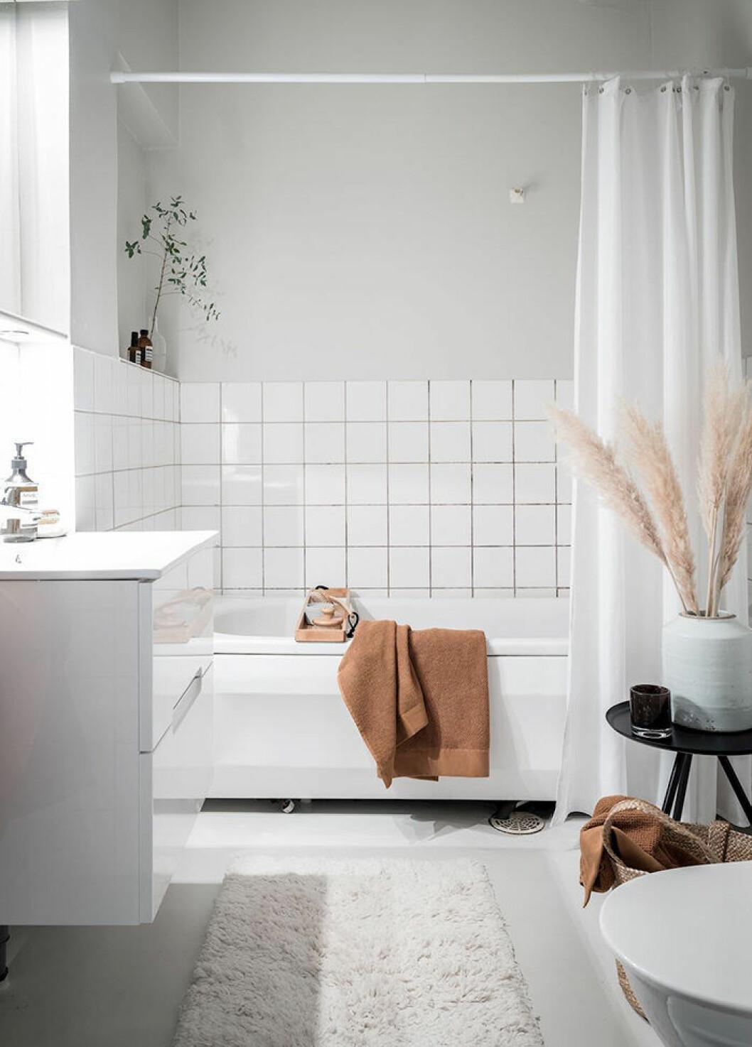 Hotellkänsla i badrummet med matta och växter