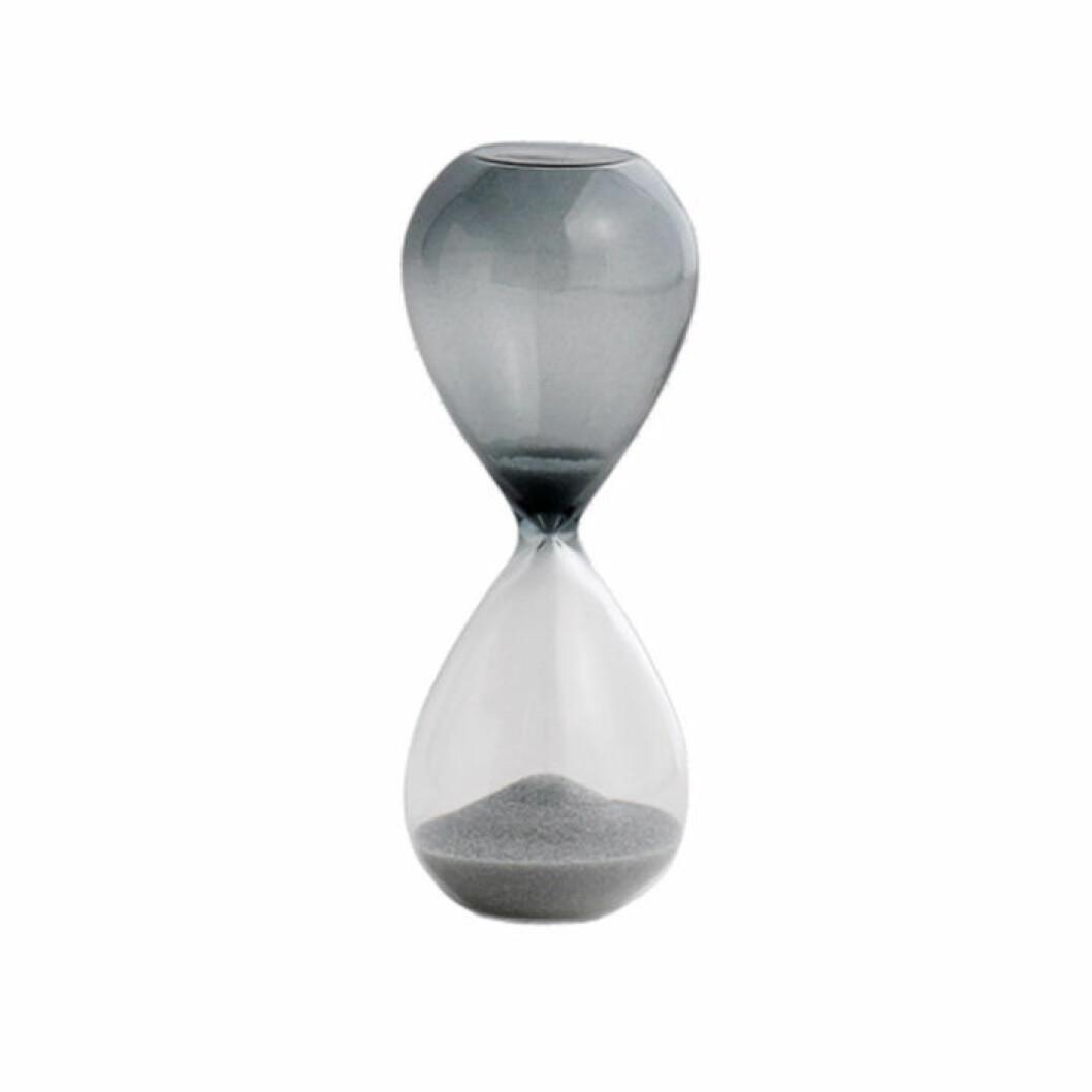 Dekorativt timglas i delvis färgat glas och med grå sand
