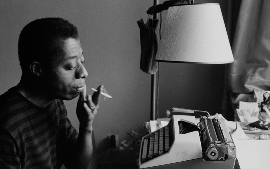 Baldwin håller i en cigarett och tänker framför en skrivmaskin.