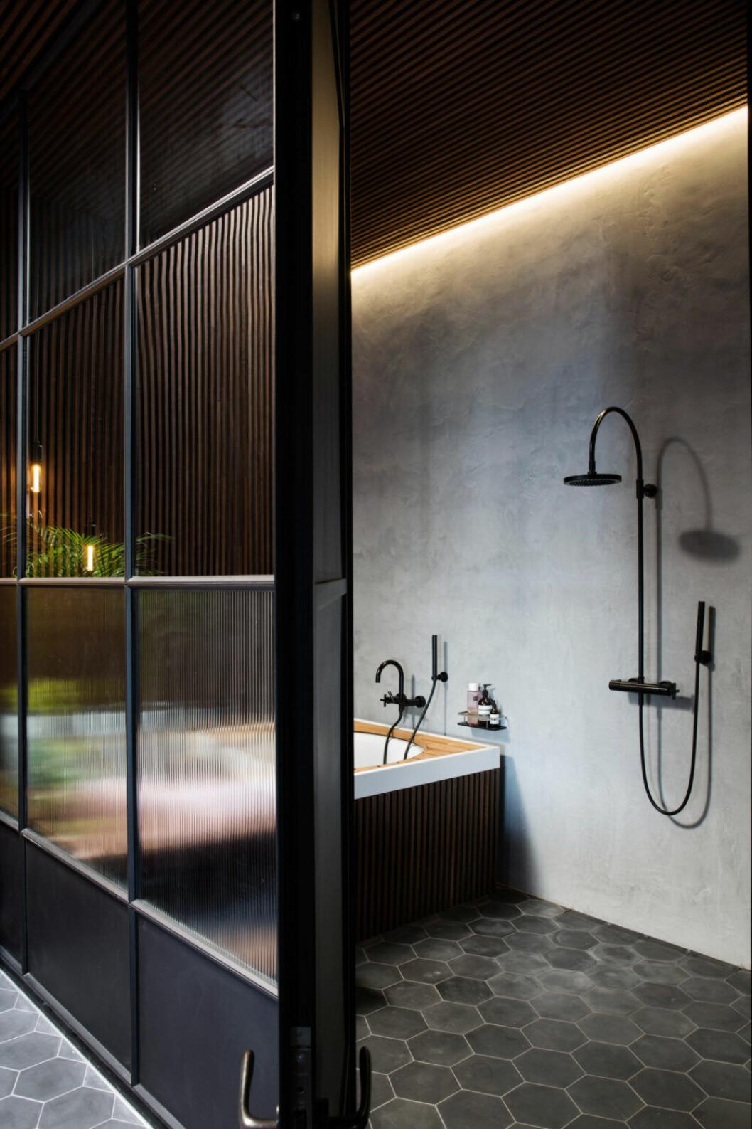 Stort badrum med skiljevägg med frostade glas och olika nyanser av svart