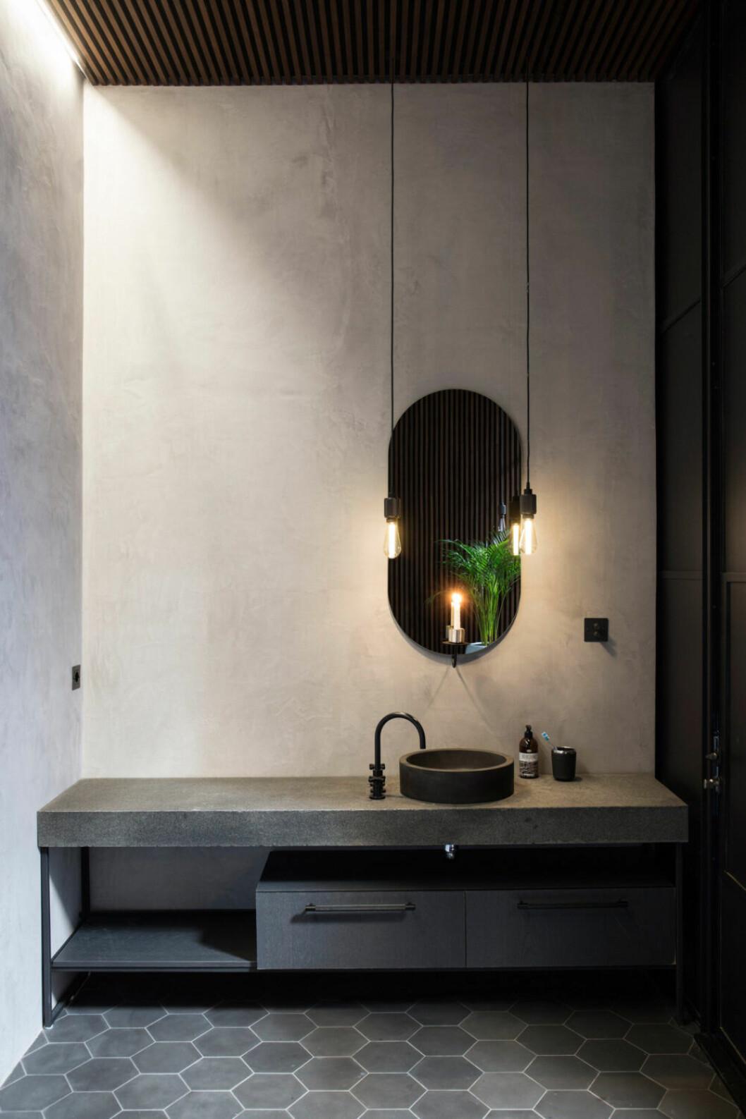 Badrum i mörka, jordiga toner och spegel från Friends & Founders