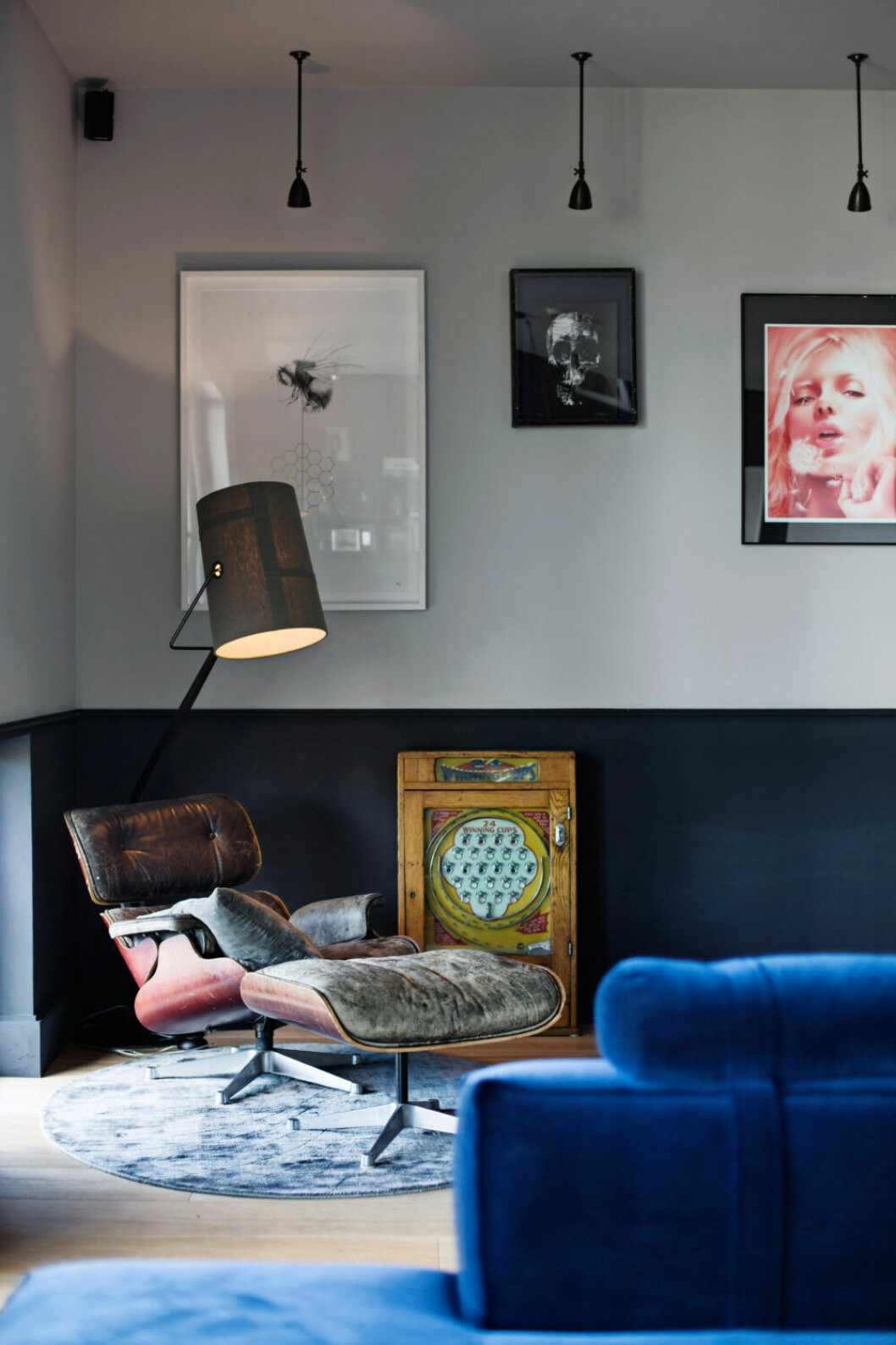 Ombonad hörna i blåa toner med fåtölj och lampa i industriell stil