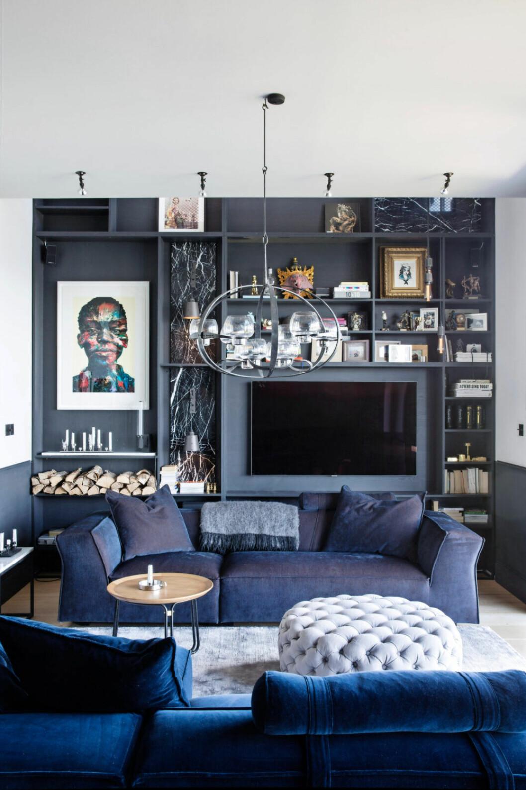 Mäktig platsbyggd bokhylla i blått med soffa i samma blåa nyans och en ljusblå sittpuff
