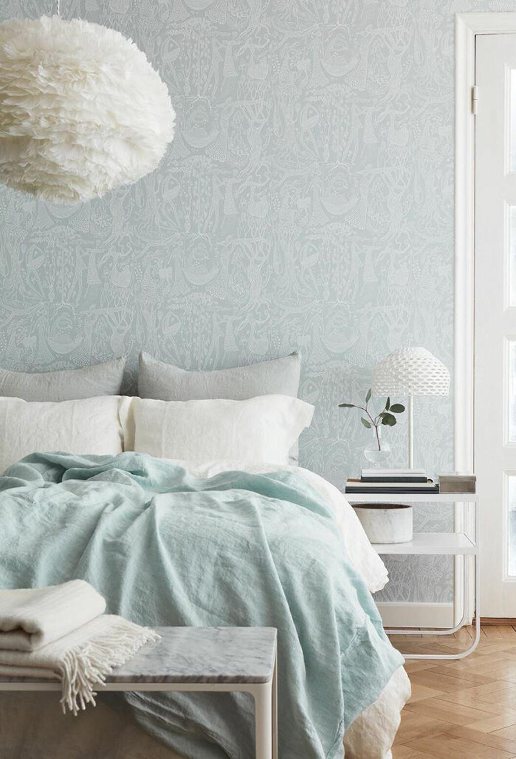 Harmoniskt sovrum med ljusblå, mönstrad tapet