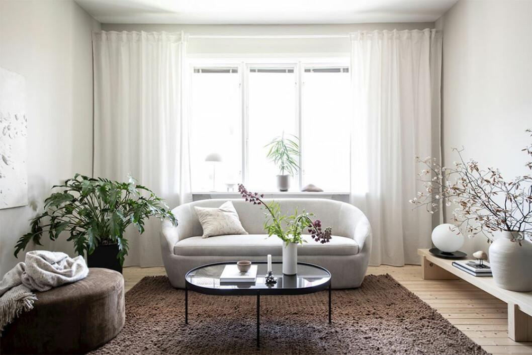 Vardagsrum med soffa och sittpuff i beige och brunt