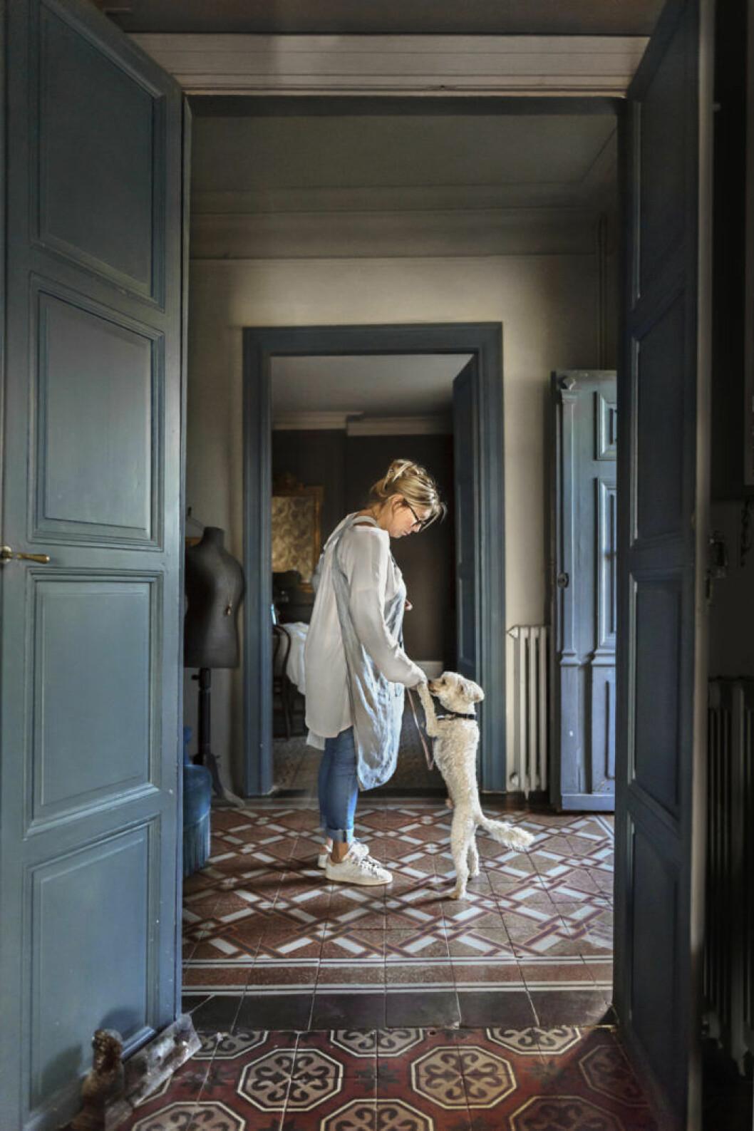Mönstrat golv, kvinna med hund, blå dörr