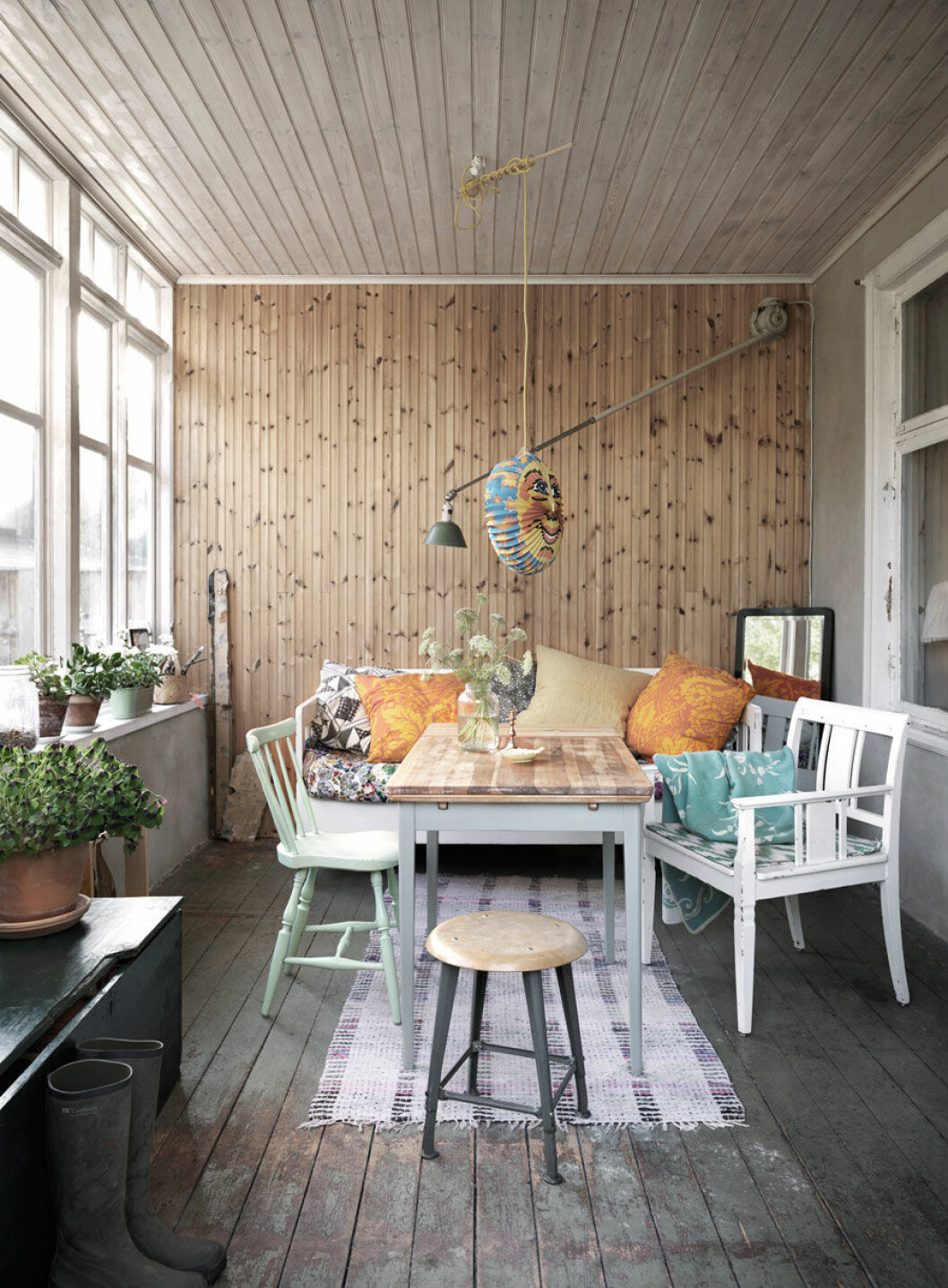 Matplats med trävägg, stolar och färgglada textilier