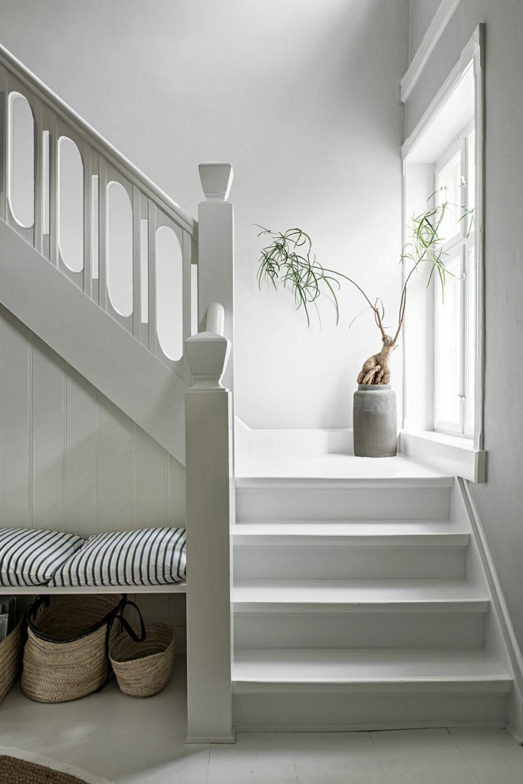 Vit trappa, bänk i hall med randiga dynor