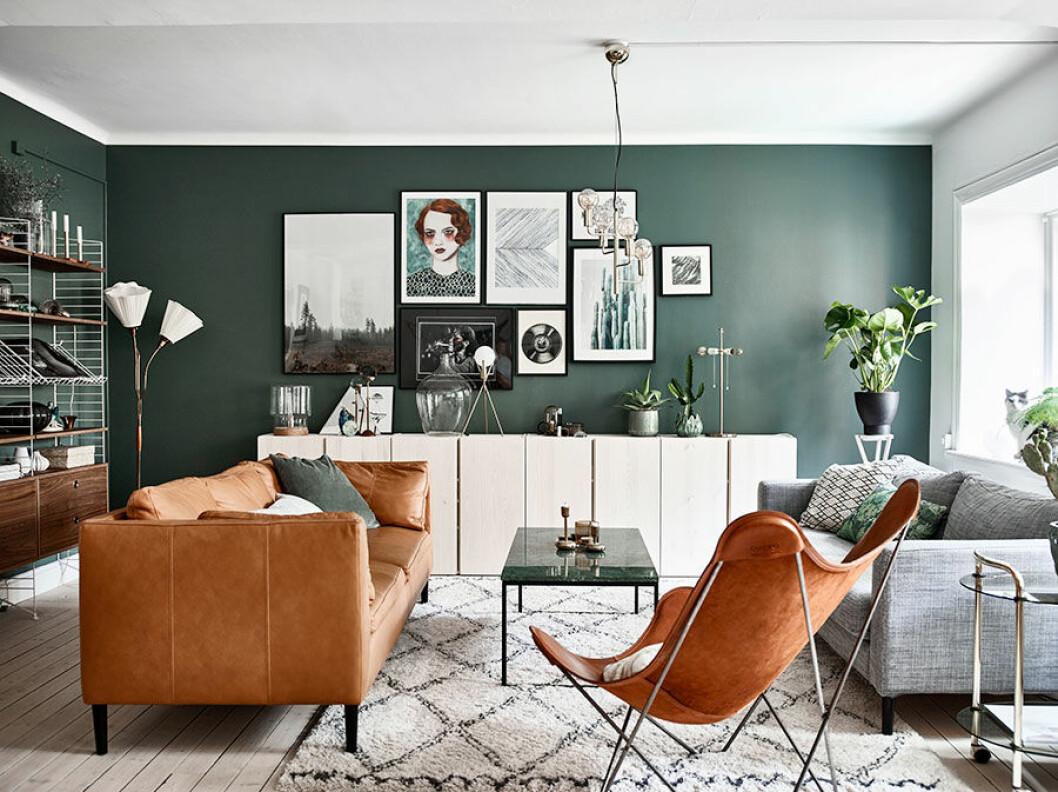 I vardagsrummet har väggarna målats i en behaglig grön kulör ur kollektionen Balance från Jotun. Den sköna gröna nyansen sätter en trivsam stämning samtidigt som den lyfter både möbler, tavlor och inredningsaccessoarer. Sofforna är från Ikea med nya ben från Prettypegs. Även skåpen Ivar längs väggen kommer från Ikea och har betsats i vitt. String-hyllorna är nyproducerade i valnöt och den trearmade lampan är köpt på Myrorna. Soffbord från Bolia, matta från Ellos och fladdermusfåtöljen är köpt på Artilleriet. Den stora tavlan längst till vänster är från Fine Little Day och bredvid den ett verk av konstnär Sofia Bonati. De övriga tavlorna är en blandning av egengjort, resefynd, Vanilla Fly och Urban Outfitters.