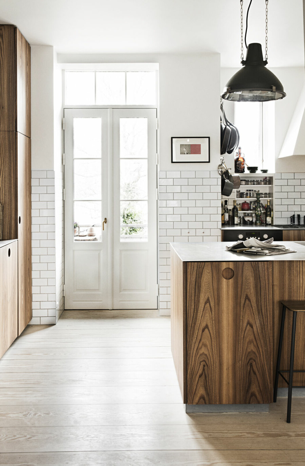 Köket med mörka träluckor i kontrast till vitt kakel som löper upp på väggarna