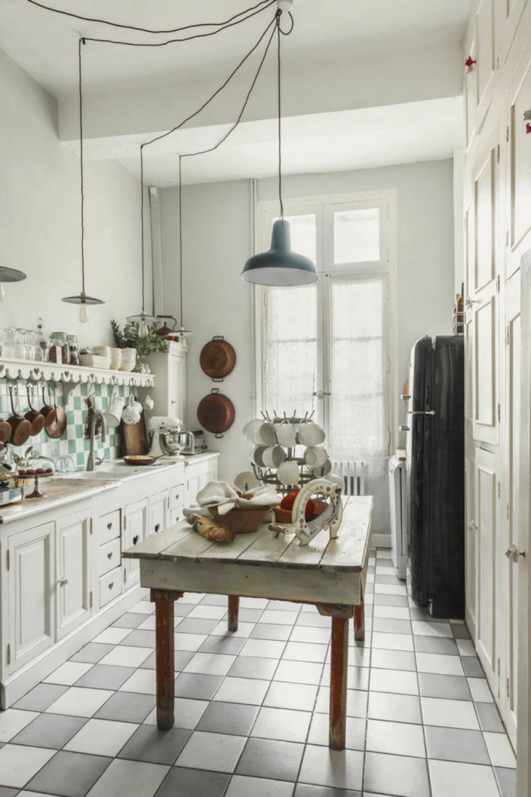 Stort och ljust kök med rutigt golv. Lantlig stil, rustikt träbord