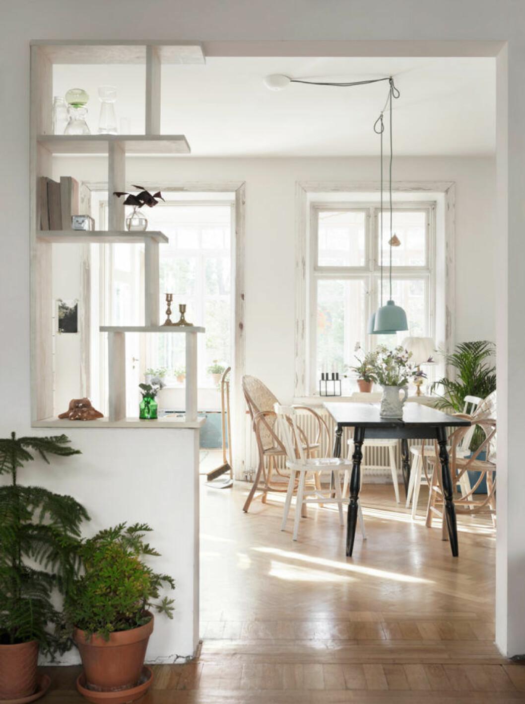 Matplats med svart matbord och stolar i vitt och trä