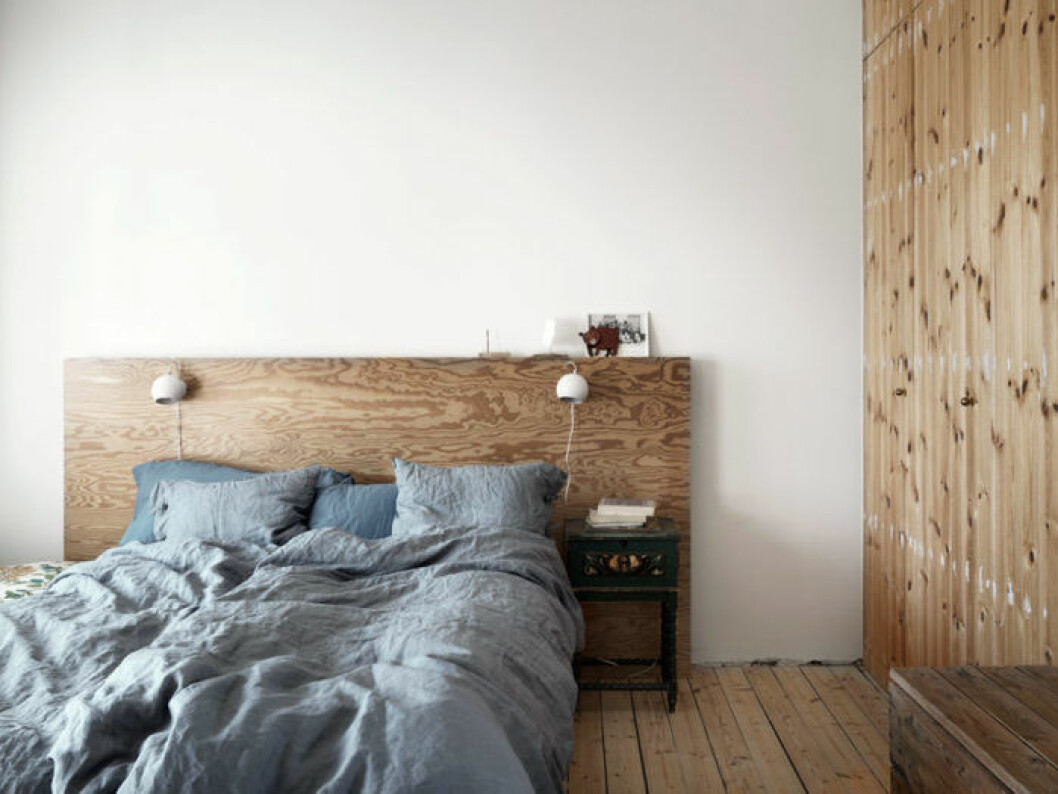 Sovrum med träväggar, trägolv och sänggavel i trä