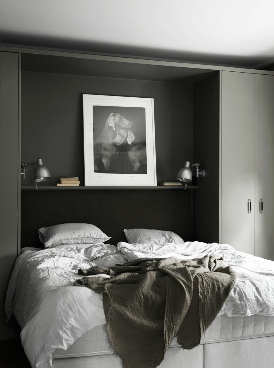 """Sovrum med platsbyggda garderober runt sängen samt inbyggt """"sängbord"""" över huvudändan."""