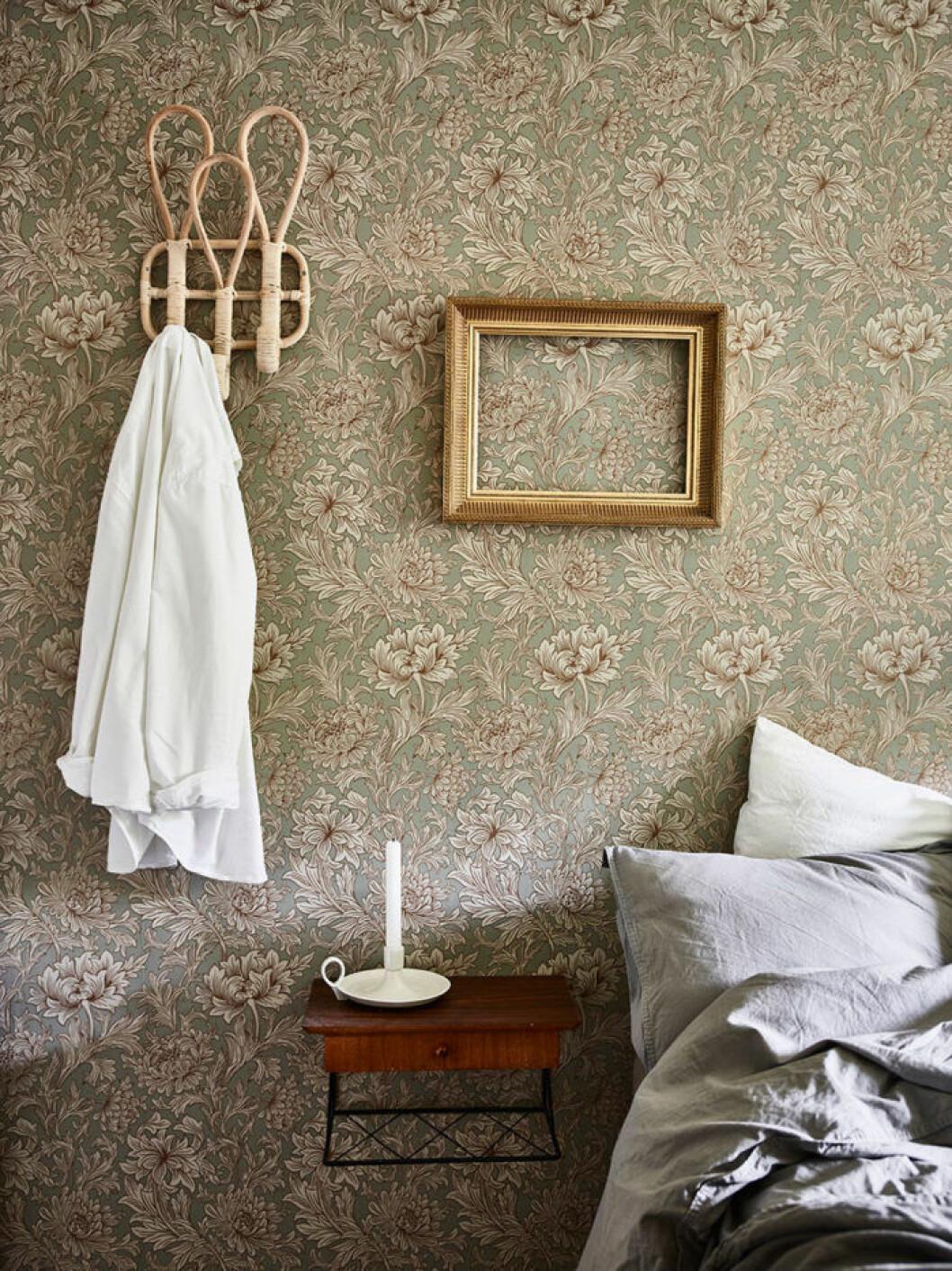 Sovrum med blommig tapet och bphemiska inredningsdetaljer