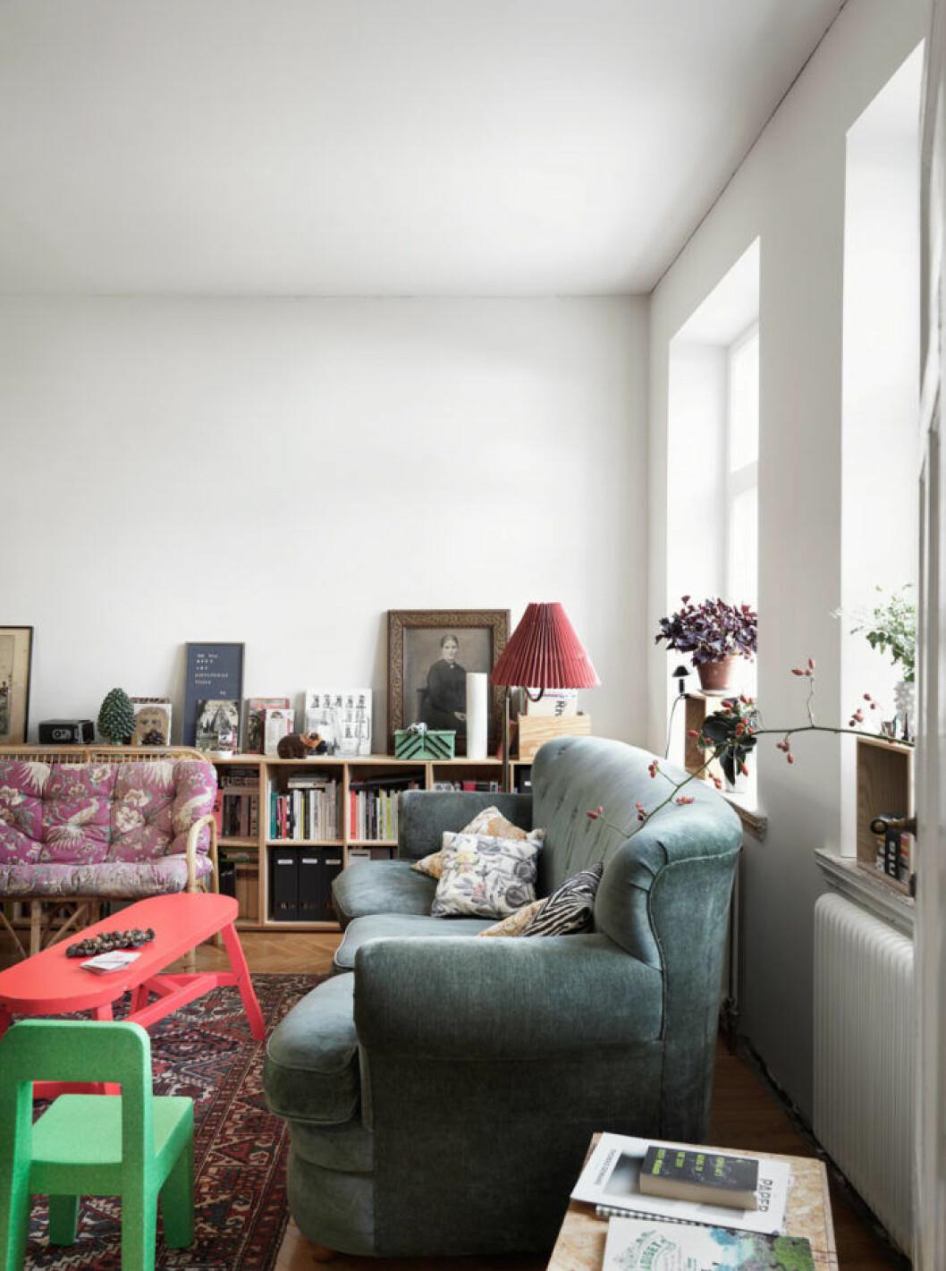 Vitmålat vardagsrum med färgglada möbler