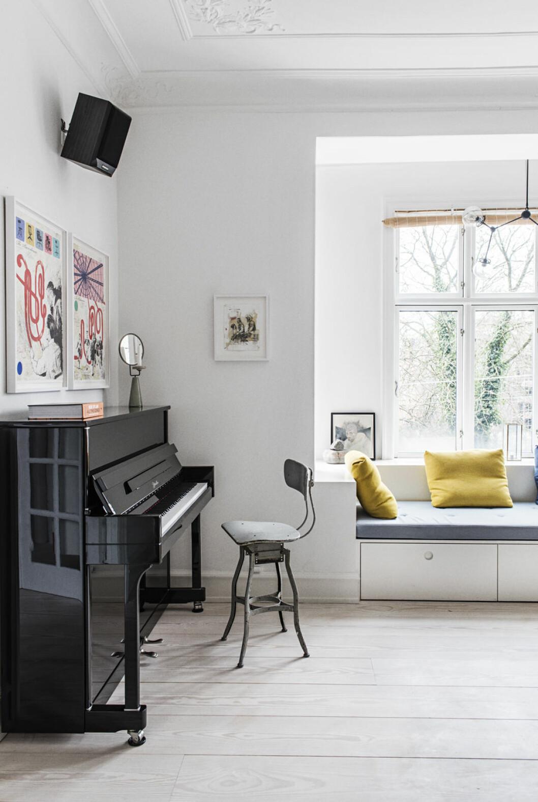 Piano och platsbyggd bänk vid fönstret