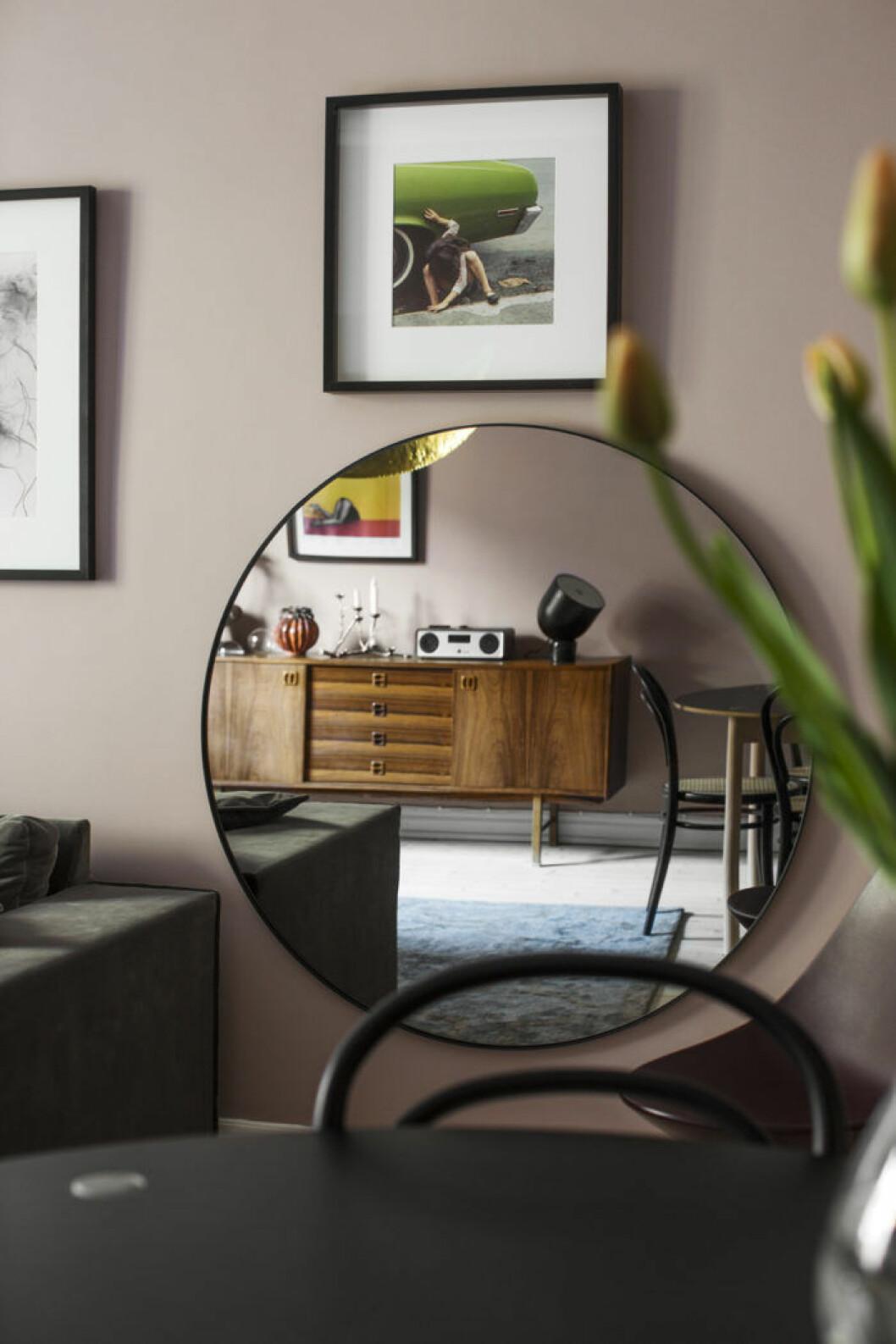 rund spegel i vardagsrummet med reflektion från sidobordet