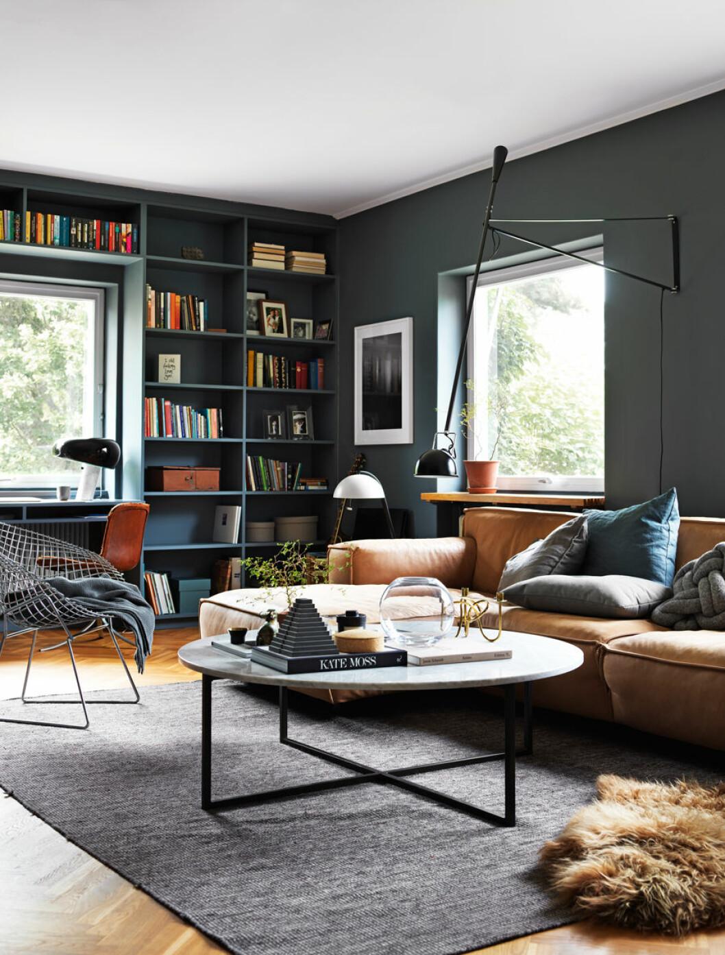 Vardagsrum med blåa väggar och en platsbyggd bokhylla i samma färg.
