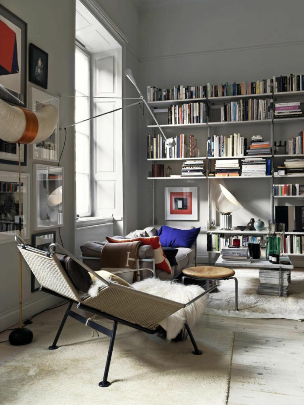 Vardagsrum med bokhylla, design fåtölj, tavelvägg