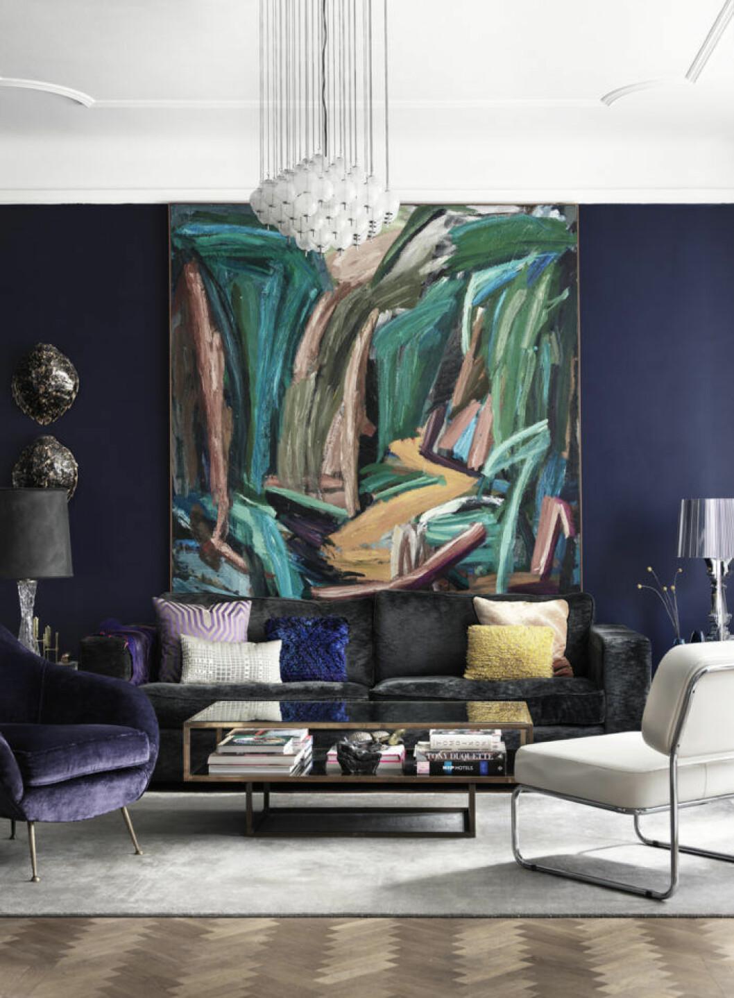 Stor abstrakt tavla i vardagsrum med färgglada sammetskuddar i mörkgrå sammetssoffa.