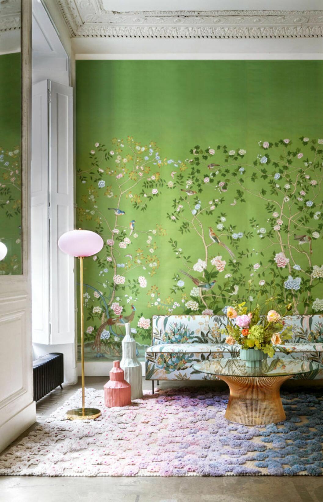 Limegrön tapet med pastellfärgade blommor och pastellfärgad matta