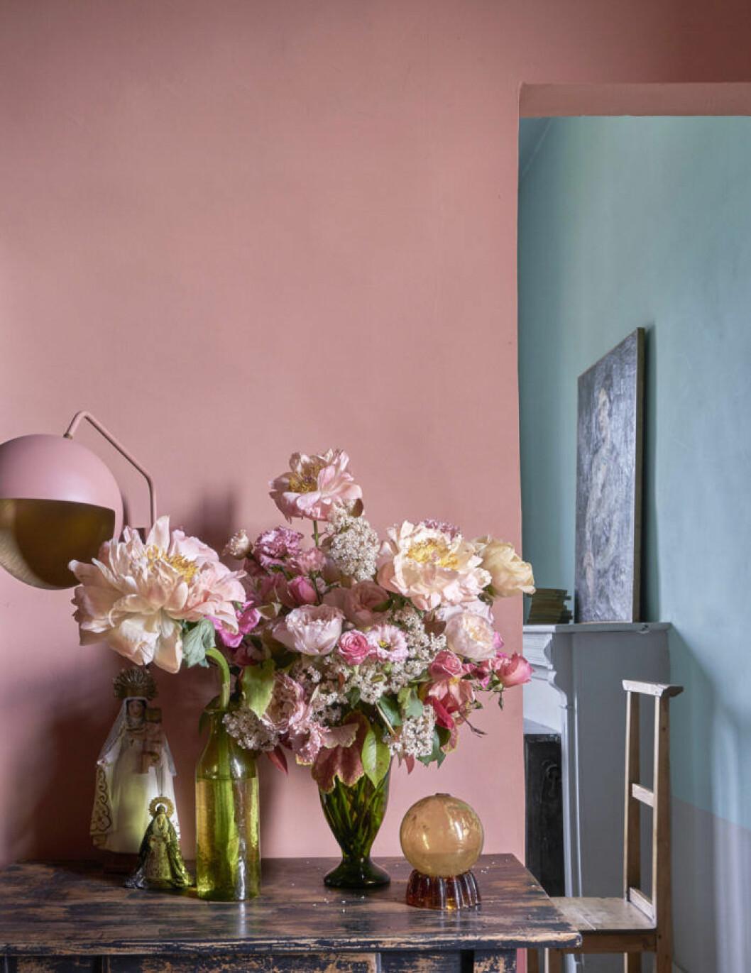 Rosa vägg, rosa bordslampa, stor bukett med rosa blommor