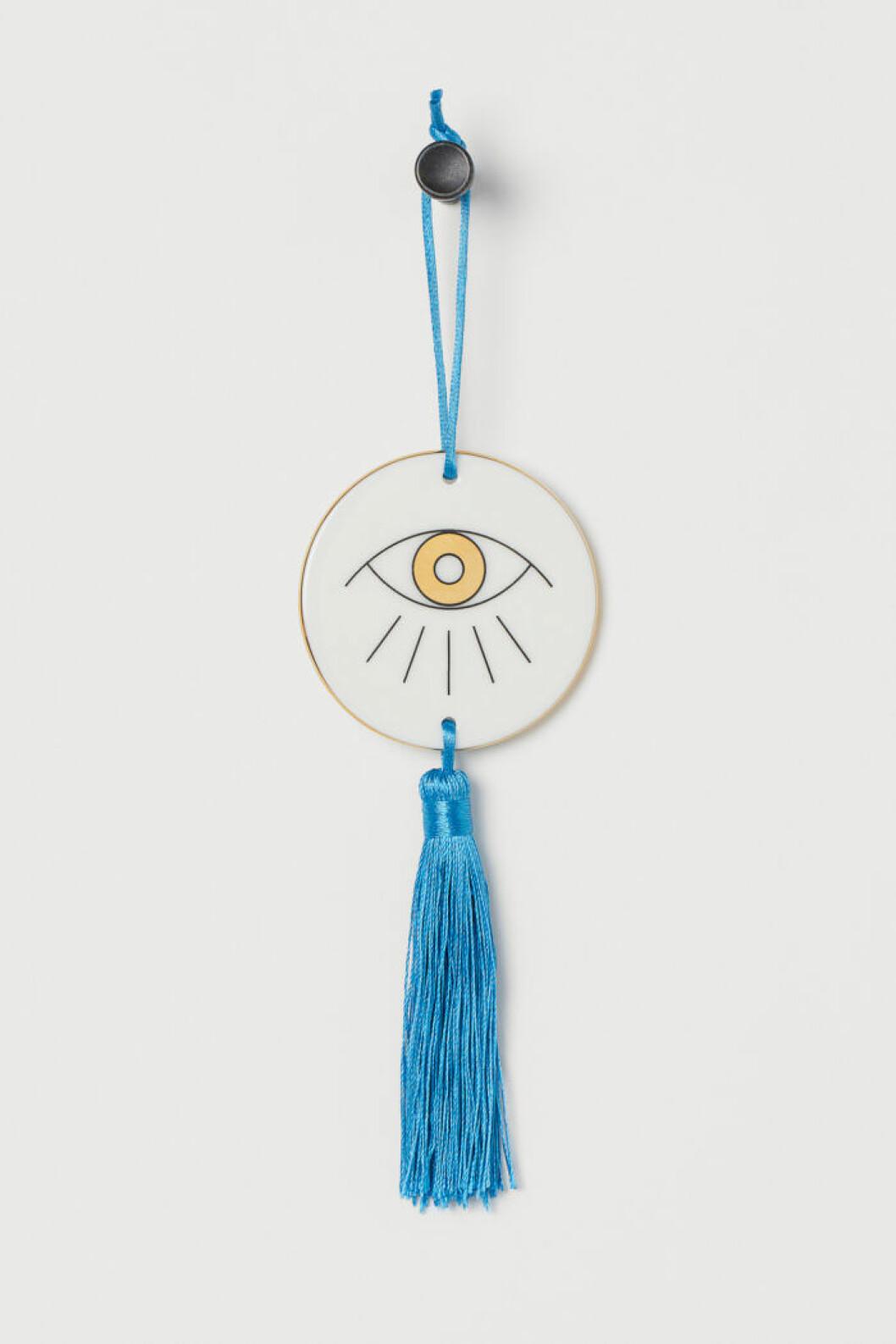 Inredningsdetalj med öga och blå tofs från Jonathan Adler x H&M