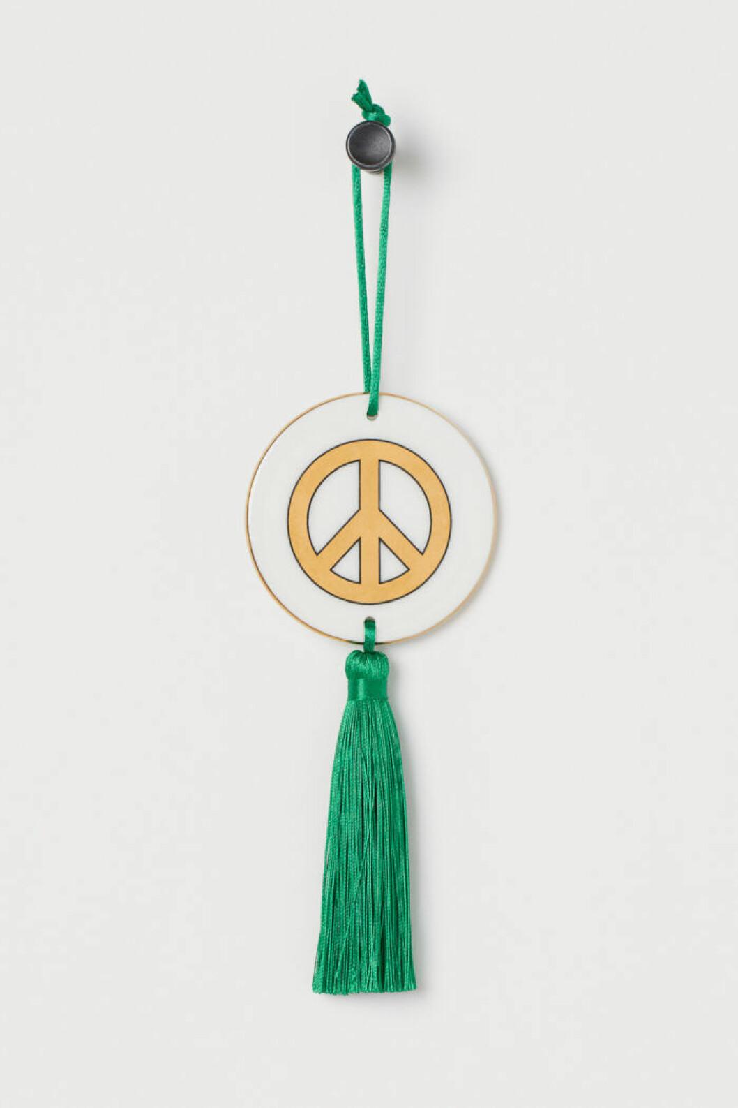 Inredningsdetalj med peacemärke och grön tofs