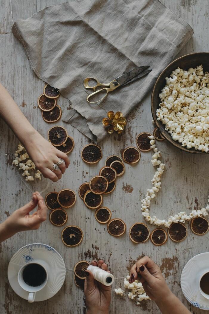 Julpyssel med hamgjorda popcorngirlanger och torkade apelsingirlanger