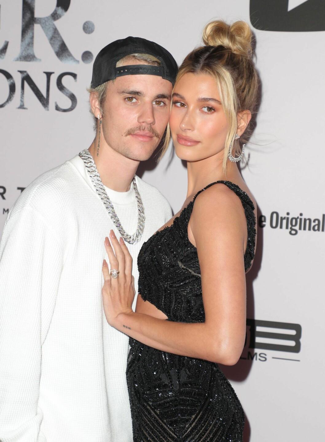 Halvkroppsbild på Justin Bieber och Hailey Bieber som står vända mot varandra och kramas