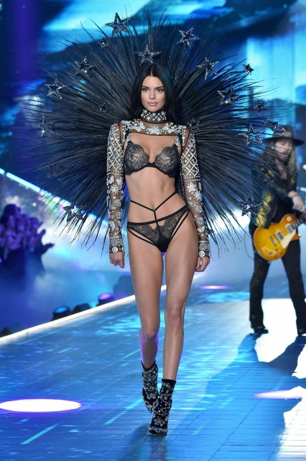 Kendall Jenner går på en catwalk iklädd svarta underkläder och stora svarta vingar på ryggen