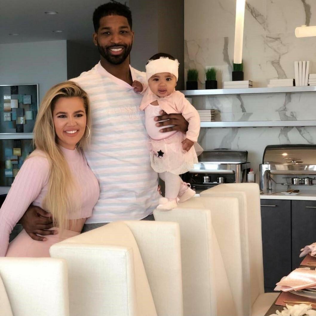 Khloé Kardashian och Tristan Thompson står bakom några stolar vid ett köksbord. Tristan håller en arm runt Khloé och håller dottern True med den andra