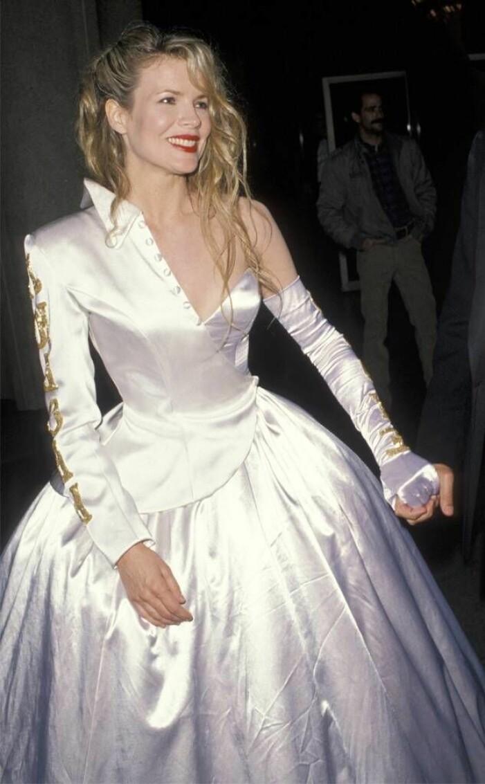 Kim Basinger i vit klänning med en arm
