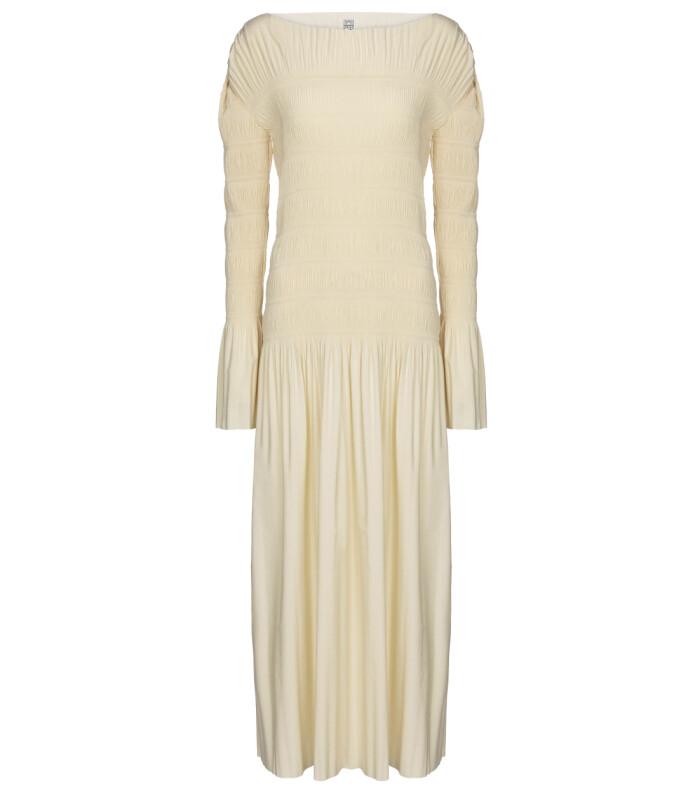 Klänning med plisserade drag i vacker krämig nyans.