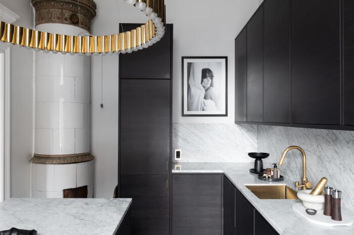 Kök med kakelugn och köksö hos Petra Tungården