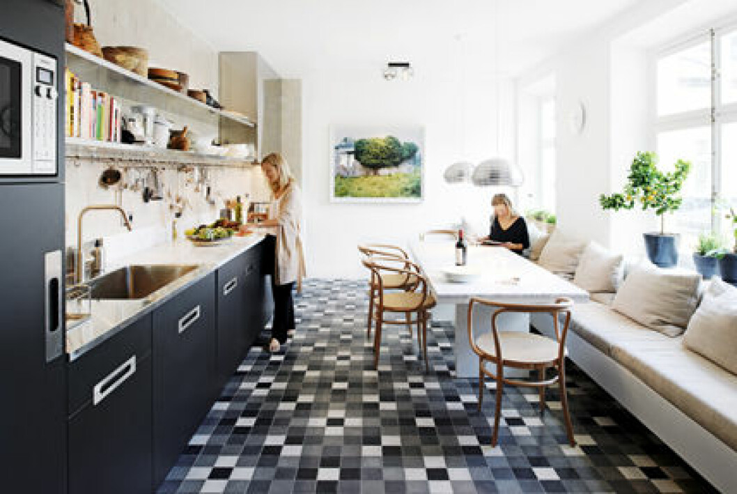 Kök med svarta luckor och ett mönstrat golv. Köket inklusive marmorbordet är ritat av Björn Aaro.