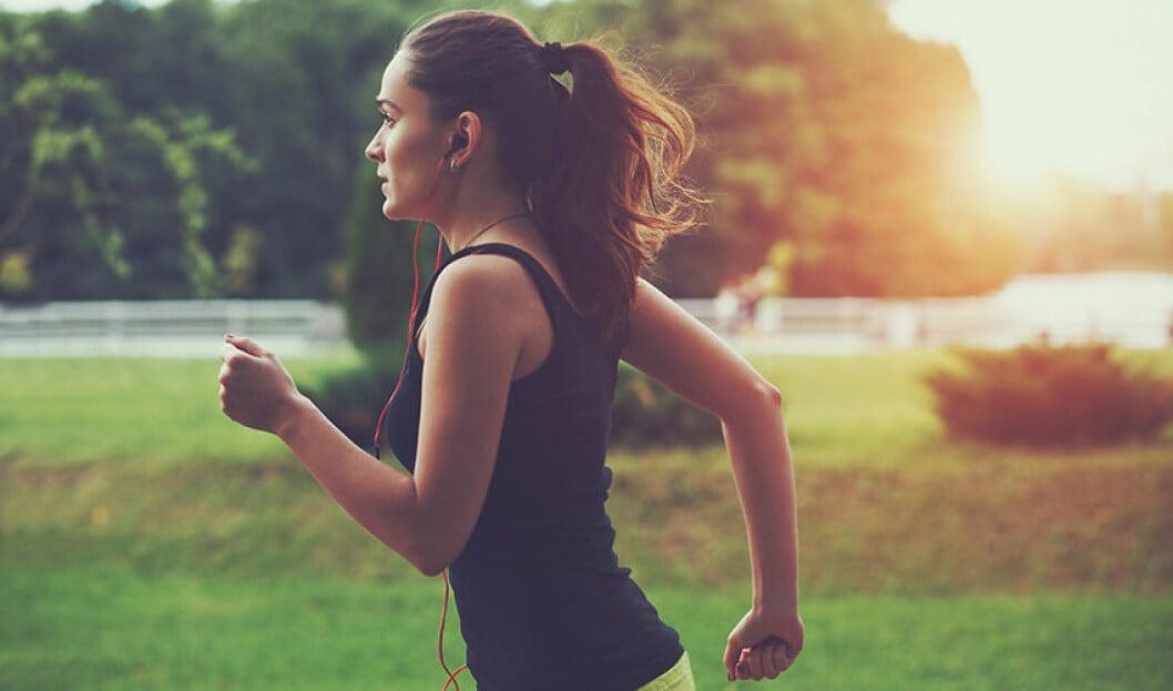 Kvinna i solnedgång som är ute på en löprunda och springer.