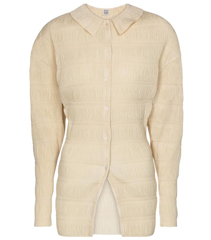 Krämvit skjorta med plisserade drag som ger en lyxig känsla mot kroppen. S