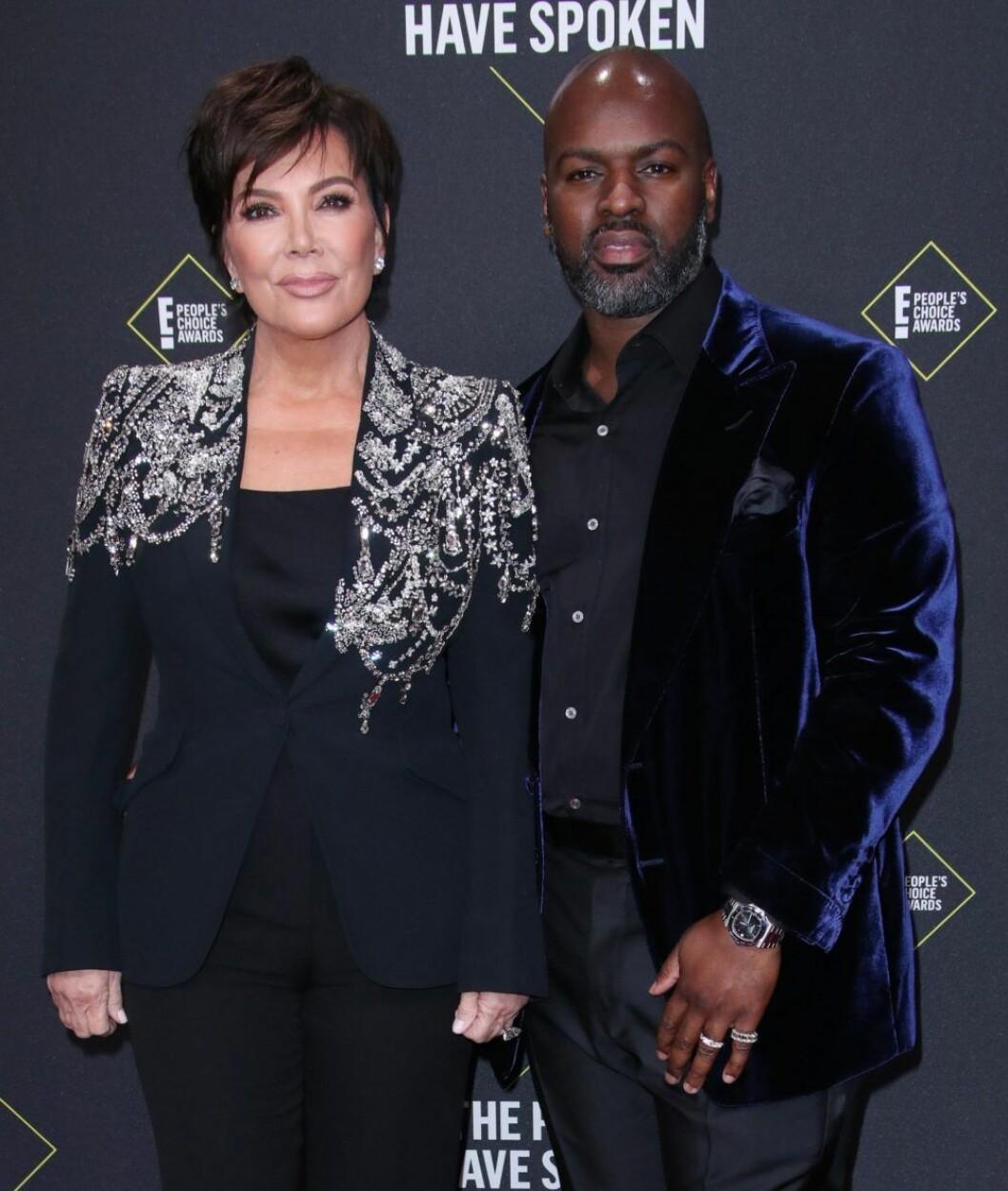 Kris Jenner och Corey Gamble poserar ihop på röda mattan iklädda mörka kläder