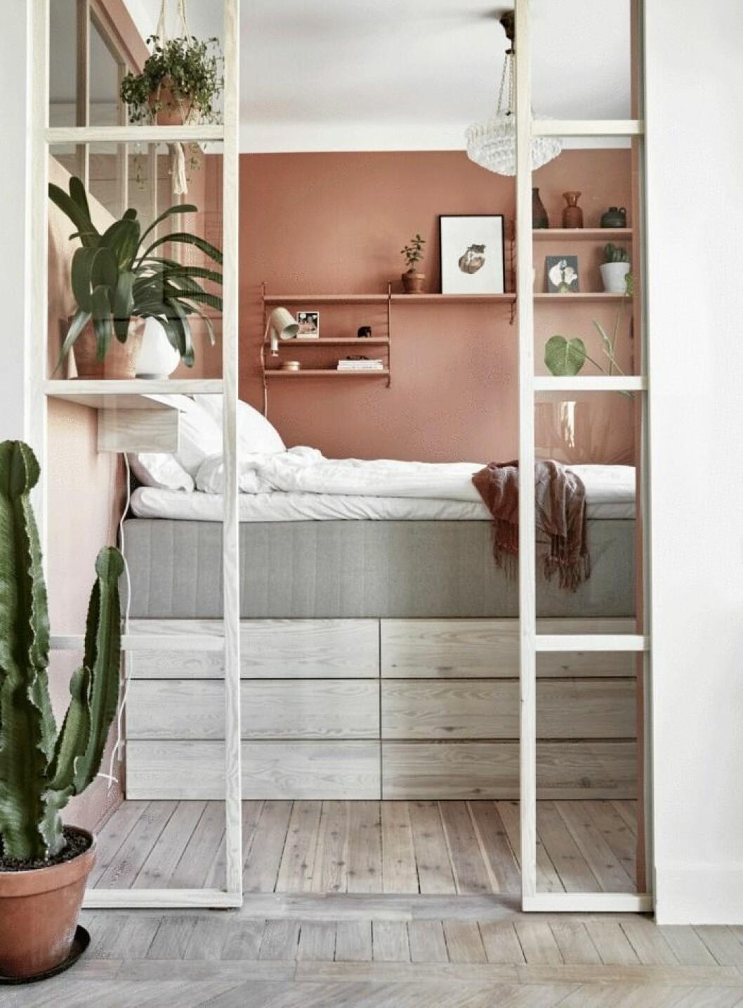 Stämningsfull sovplats i rosa med industriglas i vitt