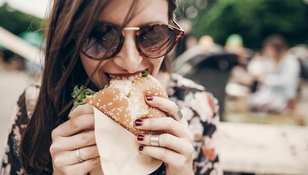 Kvinna äter skräpmat
