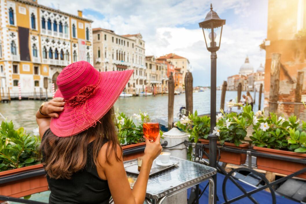 Kvinna dricker bubbel vid Grand Canale i Venedig