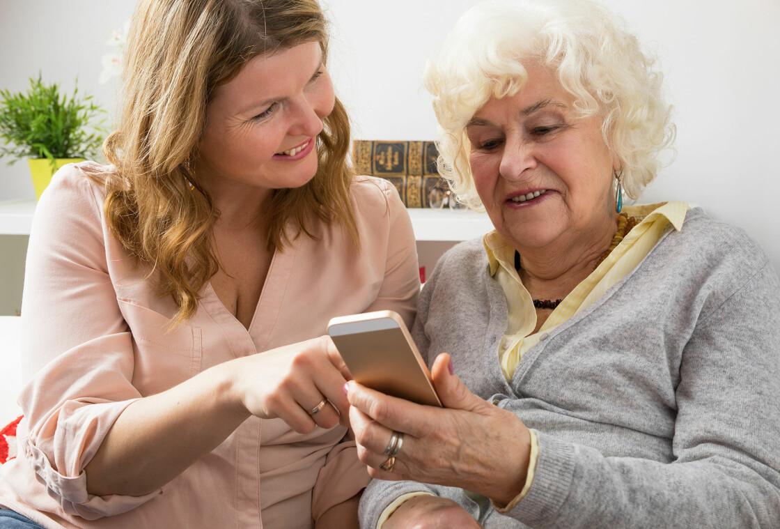 Kvinna hjälper äldre kvinna att hantera sin telefon.