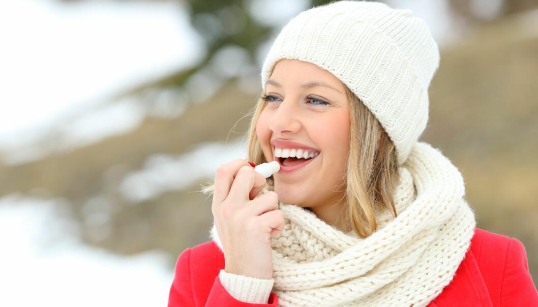 Kvinna som skyddar sina läppar med läppbalsam på vintern med ett snöig berg i bakgrunden.